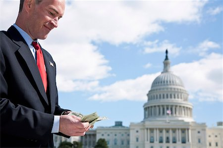 A politician counting money in front of the US Capitol Building Stock Photo - Premium Royalty-Free, Code: 653-03706779