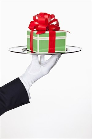 stage show - A butler presenting a gift on a silver tray, focus on hand Stock Photo - Premium Royalty-Free, Code: 653-03706823