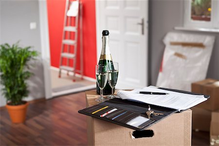Champagne and a contract in a living room with moving boxes Stock Photo - Premium Royalty-Free, Code: 653-03706851