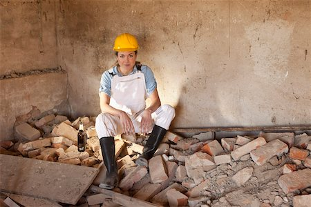 piles of work - A female construction worker sitting on rubble with a beer Stock Photo - Premium Royalty-Free, Code: 653-03844020