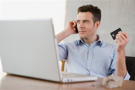 person on phone with credit card - A man holding a credit card while on the phone and using a laptop Stock Photo - Premium Royalty-Free, Code: 653-03844118