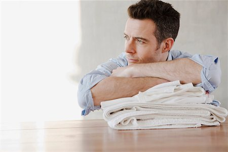 A man resting on a stack of folded laundry, day dreaming Stock Photo - Premium Royalty-Free, Code: 653-03844119