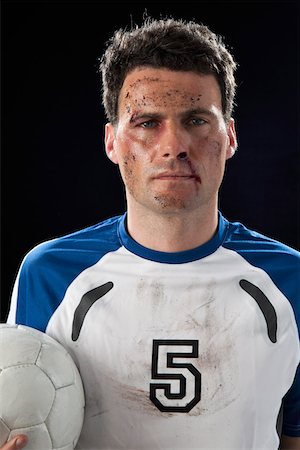 soccer player (male) - A soccer player with a bloody nose holding a soccer ball Stock Photo - Premium Royalty-Free, Code: 653-03844214