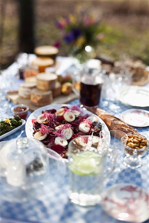 Dining table outside with focus on a dish of goat's cheese and pickled pears Stock Photo - Premium Royalty-Free, Code: 653-03844292