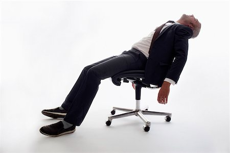 An exhausted businessman sleeping in an office chair Stock Photo - Premium Royalty-Free, Code: 653-03843146