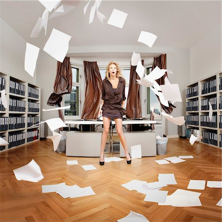 A woman standing in an office while sheets of paper blow around the room Stock Photo - Premium Royalty-Free, Code: 653-03843306