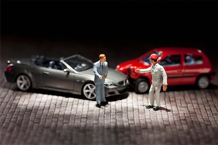 Two miniature figurine men arguing over their miniature crashed cars Stock Photo - Premium Royalty-Free, Code: 653-03843565