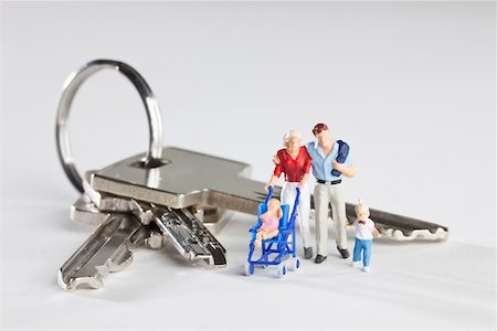 A young family of miniature figurines standing next to house keys on a key ring Stock Photo - Premium Royalty-Free, Code: 653-03843562