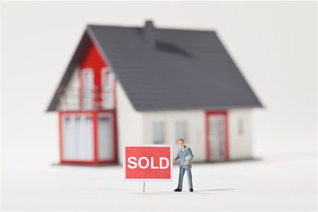 sold sign - A miniature real estate agent figurine standing next to a SOLD sign Stock Photo - Premium Royalty-Free, Code: 653-03843575