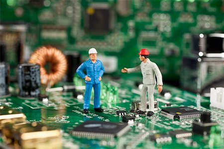 Two miniature figurine men working on a computer mother board Stock Photo - Premium Royalty-Free, Code: 653-03843576