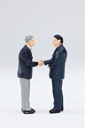 Two miniature businessmen figurines shaking hands Stock Photo - Premium Royalty-Free, Code: 653-03843577
