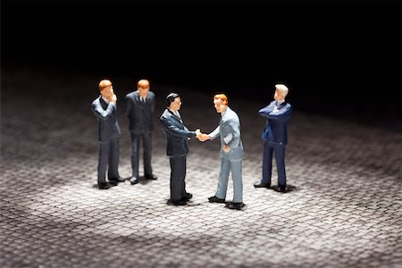 Two miniature businessmen figurines shaking hands amongst other businessmen figurines Stock Photo - Premium Royalty-Free, Code: 653-03843578