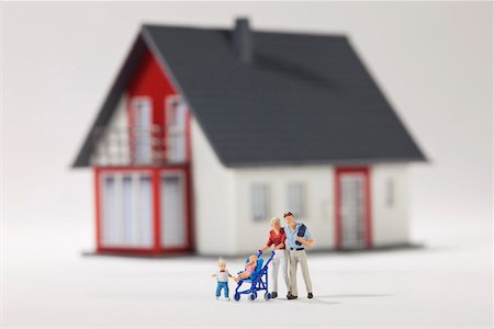 A young family of miniature figurines in front of a house Stock Photo - Premium Royalty-Free, Code: 653-03843579