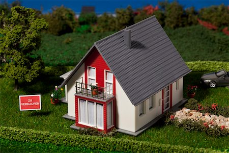 A diorama of a miniature house with a  ZU VERKAUFEN (for sale in German) sign Stock Photo - Premium Royalty-Free, Code: 653-03843581