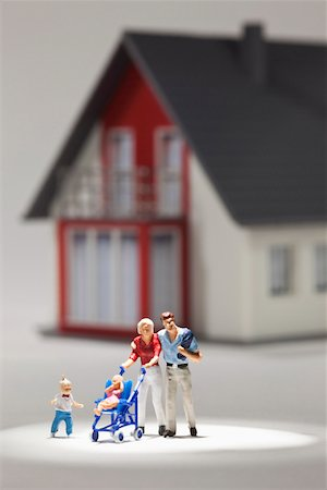 A young family of miniature figurines in front of a house Stock Photo - Premium Royalty-Free, Code: 653-03843583
