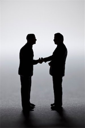 Two miniature businessmen figurines shaking hands Stock Photo - Premium Royalty-Free, Code: 653-03843590