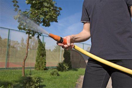 A teenage boy spraying a garden hose in a backyard, focus on hand Stock Photo - Premium Royalty-Free, Code: 653-03843766