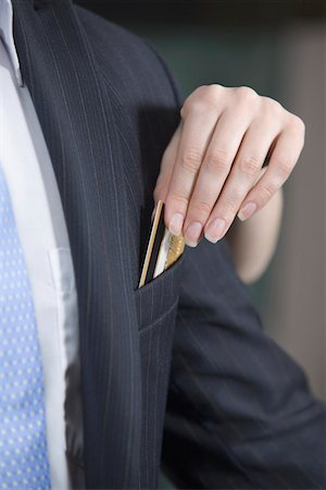 dece11 - A woman taking a credit card out of a man's jacket pocket Stock Photo - Premium Royalty-Free, Code: 653-03843789
