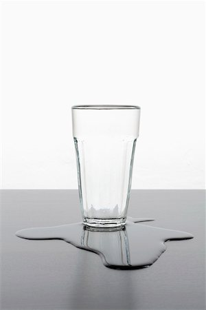 spill - An upright glass standing in a puddle of spilled water Stock Photo - Premium Royalty-Free, Code: 653-03843818