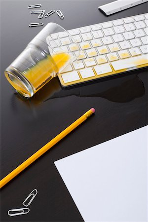 spill - A glass of orange juice spilled on a computer keyboard Stock Photo - Premium Royalty-Free, Code: 653-03843811