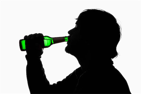 A silhouetted man drinking beer from a bottle Stock Photo - Premium Royalty-Free, Code: 653-03843887