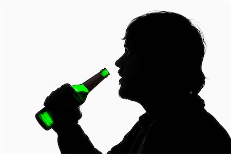 A silhouetted man about to drink from a beer bottle Stock Photo - Premium Royalty-Free, Code: 653-03843897
