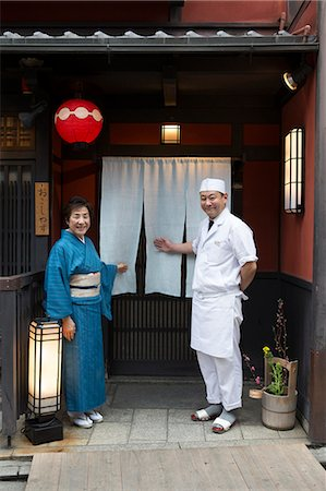 Senior Japanese hostess and cook smiling in front of Japanese restaurant Stock Photo - Premium Royalty-Free, Code: 669-08546012