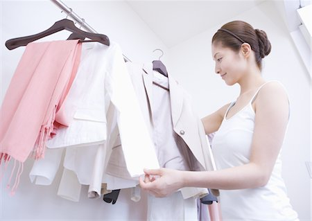 Woman in closet choosing clothes Stock Photo - Premium Royalty-Free, Code: 669-03734021