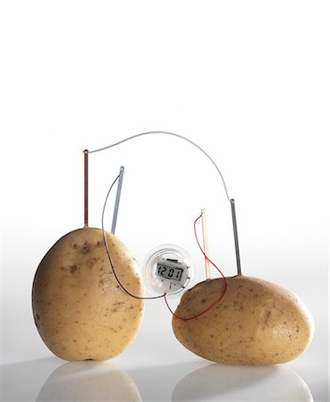reaction - Potato clock. A chemical reaction between the copper and zinc plates and the potatoes produces a small current, that is able to power a light bulb. Stock Photo - Premium Royalty-Free, Code: 679-05996490