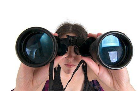 forward - Woman looks through a binoculars facing camera wide angle view Stock Photo - Premium Royalty-Free, Code: 679-05992447