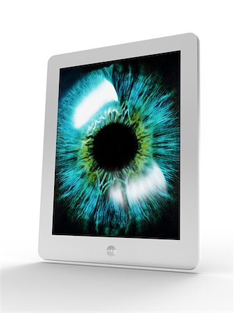 Tablet computer showing artwork of a close-up of the iris and pupil of an eye. The iris, a coloured muscular ring, regulates the amount of light that enters the eye through the pupil (black). Stock Photo - Premium Royalty-Free, Code: 679-06713876
