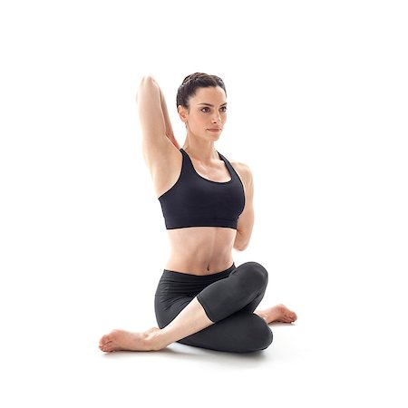 sitting - Woman practicing yoga. This is the cow's faced pose. Stock Photo - Premium Royalty-Free, Code: 679-07607055