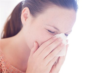 people coughing or sneezing - Young woman sneezing. Stock Photo - Premium Royalty-Free, Code: 679-07607573