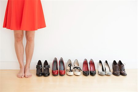 Woman standing next to a row of shoes. Stock Photo - Premium Royalty-Free, Code: 679-07607999