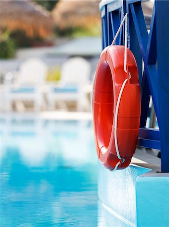 red - Life ring hanging on the railings of a hotel swimming pool. Stock Photo - Premium Royalty-Free, Code: 679-07608206