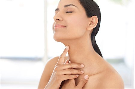 Young woman touching her neck, portrait. Stock Photo - Premium Royalty-Free, Code: 679-08009649