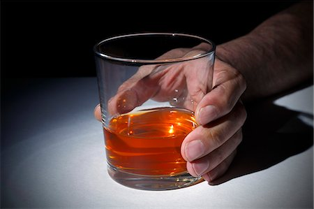 Person holding a glass of whisky, studio shot. Stock Photo - Premium Royalty-Free, Code: 679-08228397