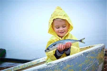 fishing - Young boy wearing raincoat holding a mackerel, portrait. Stock Photo - Premium Royalty-Free, Code: 679-08424940
