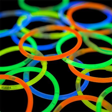 Glowstick bangles against a black background. Stock Photo - Premium Royalty-Free, Code: 679-08424961