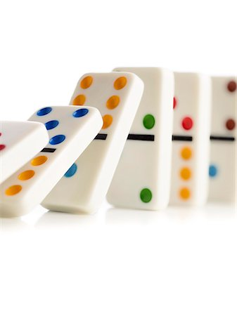 photografia - Colourful dominoes falling down against a white background. Foto de stock - Royalty Free Premium, Número: 679-08425050
