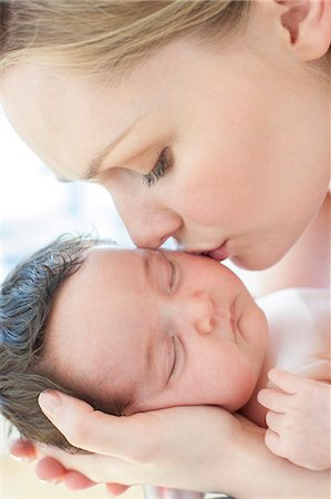 Mother kissing newborn baby girl. Stock Photo - Premium Royalty-Free, Code: 679-08581257