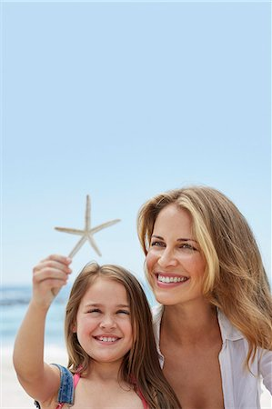 sea star - Mother with daughter on the beach with a starfish. Stock Photo - Premium Royalty-Free, Code: 679-08663752