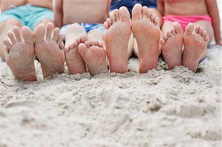 Family sitting on the beach, focus on bare feet. Stock Photo - Premium Royalty-Free, Code: 679-08663774