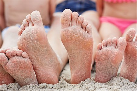 Family sitting on the beach, focus on bare feet. Stock Photo - Premium Royalty-Free, Code: 679-08663775