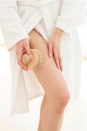 Young woman using body brush on leg. Stock Photo - Premium Royalty-Free, Code: 679-08718200