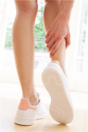 Young woman wearing white trainers, holding ankle. Stock Photo - Premium Royalty-Free, Code: 679-08718210