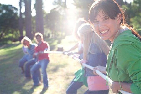 Tug of war. Woman helping her team of friends to gain control of a rope. This sport challenges the strength of two opposing teams. Stock Photo - Premium Royalty-Free, Code: 679-02684120