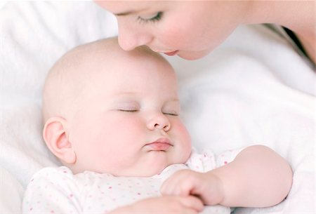 Mother and baby. Mother kissing her sleeping 7 month old baby girl on the forehead. Stock Photo - Premium Royalty-Free, Code: 679-02685319