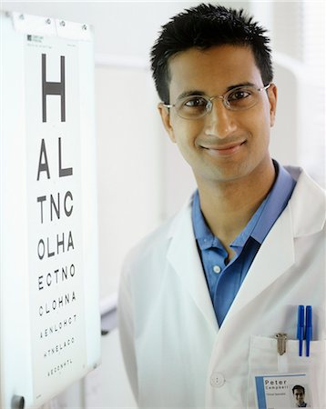 Optometrist next to an eye chart. The eye chart is used to test a person's visual acuity. Stock Photo - Premium Royalty-Free, Code: 679-02685923