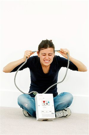 Woman joking while doing DIY. She is holding the cables to a high-voltage mains box to her head. Stock Photo - Premium Royalty-Free, Code: 679-03298382